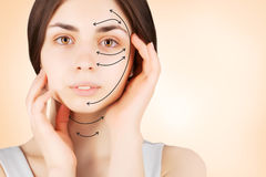 Brunette woman with  marks on face on pink. Plastic operation concept - brunette woman with  marks on face Royalty Free Stock Photography