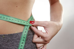 Brunette woman measuring her belly Stock Photography