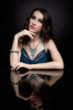 Brunette woman and mirror. Portrait of young beautiful brunette woman in jewelery at mirror table Stock Images