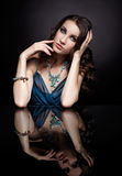 Brunette woman and mirror. Portrait of young beautiful brunette woman in jewelery sitting at mirror table Royalty Free Stock Photos