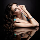 Brunette woman and mirror. Portrait of young beautiful brunette woman in jewellery at black mirror table Stock Photography