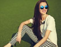 Brunette woman model in summer hipster casual clothes posing on street background in the park Stock Photos