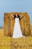 Brunette woman near hay bale. Beautiful brunette woman near hay bale in warm summer day Stock Photos