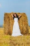 Brunette woman near hay bale. Beautiful brunette woman near hay bale in warm summer day Stock Photo