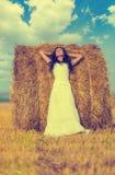 Brunette woman near hay bale. Beautiful brunette woman near hay bale in warm summer day Stock Photography