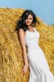 Brunette woman near hay bale. Beautiful brunette woman near hay bale in warm summer day Royalty Free Stock Photography