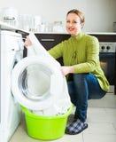 Brunette woman near washing machine Royalty Free Stock Image