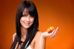 Brunette woman with nectarine on orange background Stock Photo