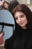 Brunette woman with new hairstyle looking at mirror. In hair salon. Portrait of young brunette woman looking at mirror by hairstylist. Girl admiring impressed Royalty Free Stock Photos