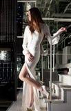 Brunette woman in night club - long white dress Stock Image