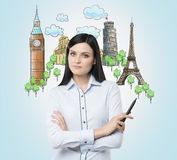 A brunette woman offers the visiting of the most famous cities in Europe. The concept of tourism and sightseeing. Light blue backg Royalty Free Stock Images