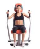 Brunette woman on orange  hydraulic exerciser Stock Image