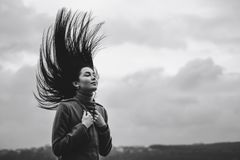 Brunette woman outdoor with blowing up hair stock photo