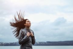 Brunette woman outdoor with blowing up hair royalty free stock photo