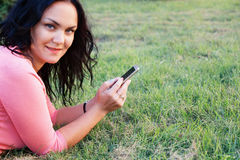 Brunette woman outdoors with a mobile phone Stock Image