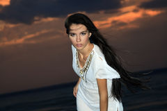 Brunette woman over dusk sky at sunset Stock Photography