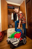 Brunette woman packing clothes in big suitcase Royalty Free Stock Image