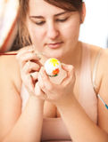 Brunette woman painting white easter egg Royalty Free Stock Images