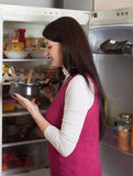Brunette woman with  pan near opened refrigerator Stock Photography