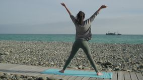 Brunette woman is performing warrior position and changing asanas on beach stock footage