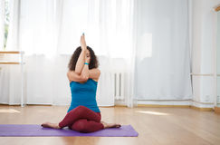 Brunette woman performing yoga asana in gym stock image