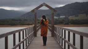 Brunette woman photographer with orange trench coat on a bridge. With a camera royalty free stock photos