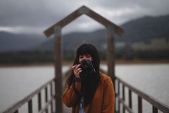Brunette woman photographer with orange trench coat on a bridge stock image