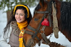 Brunette woman portrait with horse in winter Stock Photography