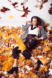 Brunette woman portrait in lying autumn leaves Stock Images