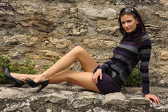 Brunette woman posing on a rock Stock Images