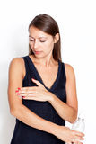 Brunette woman putting lotion on. Mid-adult tainted woman putting lotion on her arm stock photography