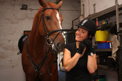 Brunette woman putting on riding helmet before riding horse Royalty Free Stock Photos