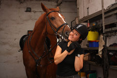 Brunette woman putting on riding helmet before riding horse Stock Image