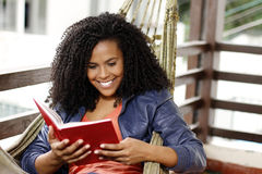 Brunette woman read book on hammock Stock Photos