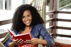 Brunette woman read book on hammock Stock Images