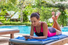 Brunette woman read electronic book near pool. Beautiful young slim brunette woman read electronic book - ebook and sunbathe in the tropical swimming pool stock image