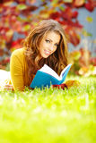 Brunette woman reading a book in the autu Stock Image