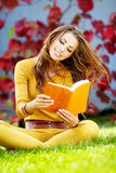 Brunette woman reading a book in the autu Royalty Free Stock Image