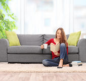 Brunette woman reading a book and drinking coffee Stock Image