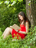 Brunette woman reading a book in the park Royalty Free Stock Images