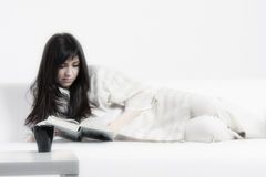 Brunette woman reading on couch Stock Photos