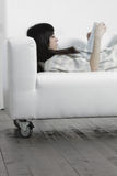Brunette woman reading on sofa Stock Photography