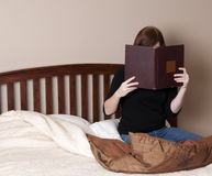 Brunette Woman Reads in Bed Stock Images