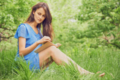 Brunette woman reads a book in park Stock Photo