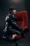 Brunette woman in red armchair stock photo