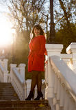 Brunette woman in red coat standing on stone stairs at sunny day Royalty Free Stock Photos