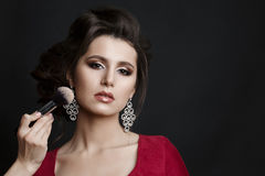 Brunette woman in red dress seductive posing at studio when incognito makeup artist making blush on cheekbone with brush. Unhappy Stock Images