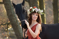Brunette woman in a red dress with a wreath of flowers Royalty Free Stock Image