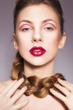 Brunette woman with red full lips and red lines on her eyelids and braid hairstyle Royalty Free Stock Photography
