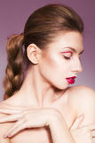 Brunette woman with red full lips and red lines on her eyelids and braid hairstyle Stock Photography
